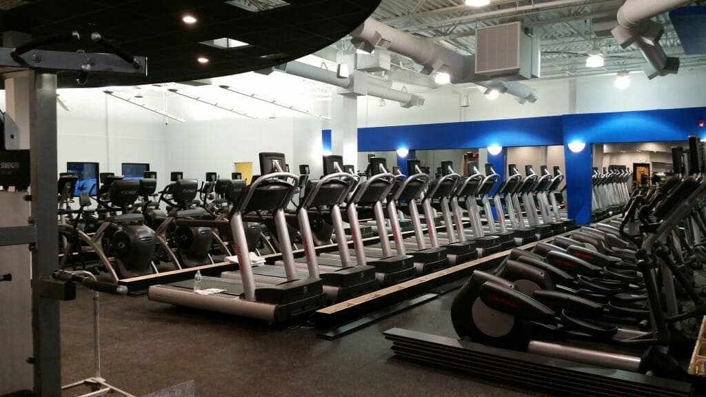 Rows of workout equipment including treadmills and stationary bikes