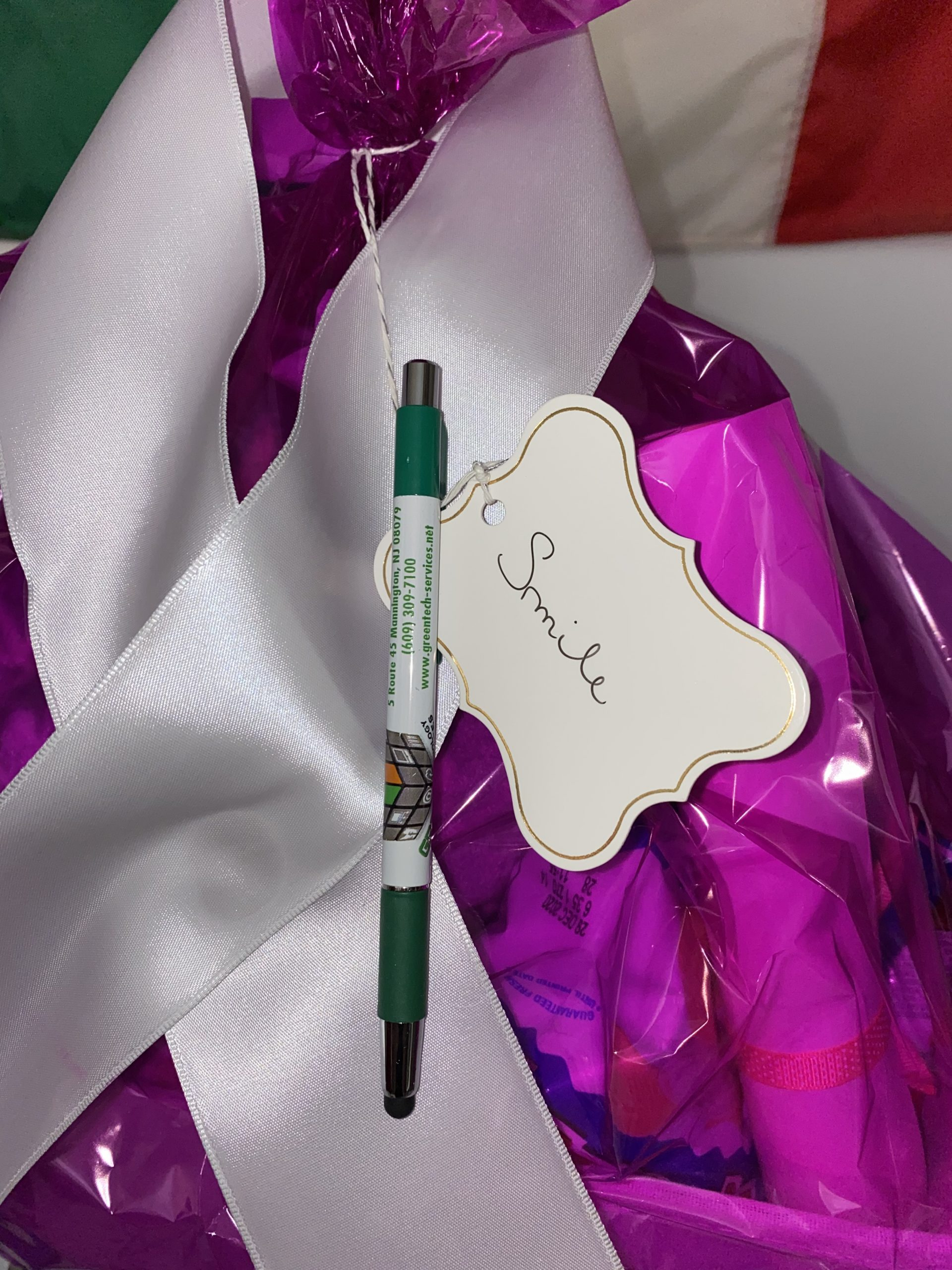 Closeup of Ribbon with company pen and tag saying Smile