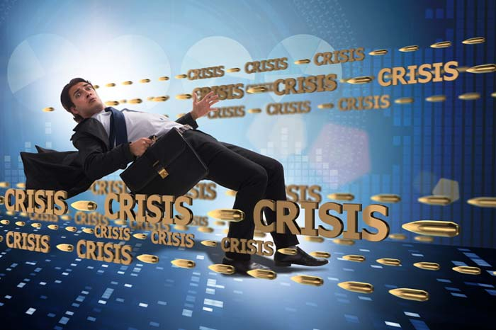 """Worried businessman falling backward with the word """"crisis"""" surrounding him"""
